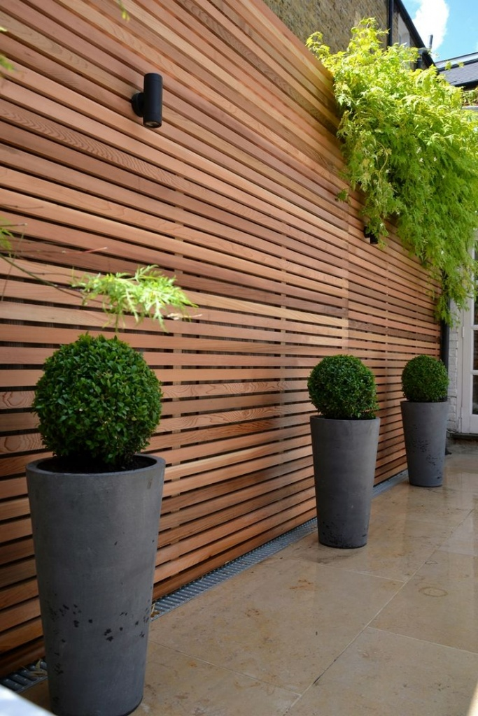 Grey concrete pots for outside with wood fence
