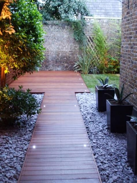 black square planters line wooden path
