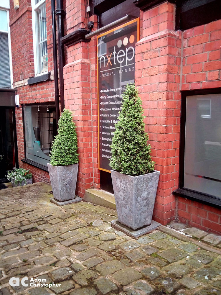 tapered stone planters against red brick 1000