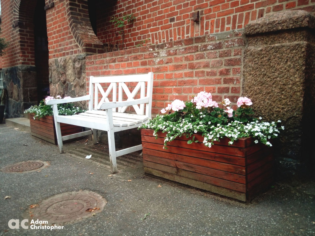 wooden box planters aside white bench on the street