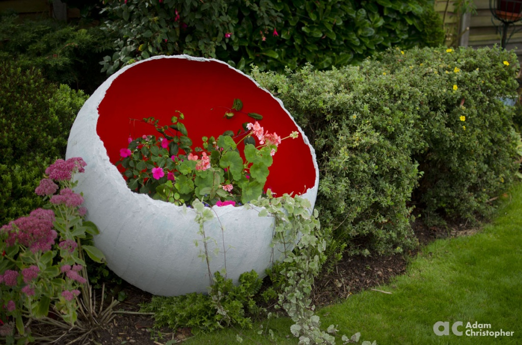 red-egg-sculpture-planter-with-trailing-plants-logo